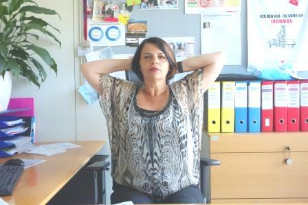 Donna seduta alla scrivania con le mani incrociate dietro alla nuca e i gomiti aperti