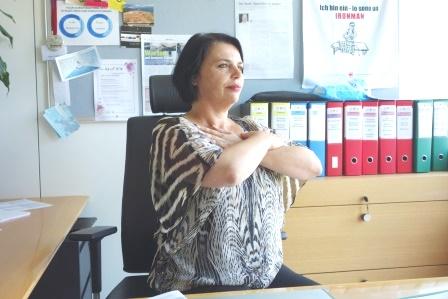 Donna seduta alla scrivania con le mani incrociate sul petto all'altezza delle clavicole