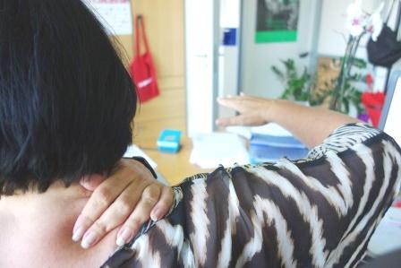 Donna seduta alla scrivania si massaggia i muscoli di collo e spalla destra con la mano sinistra, mentre tiene il braccio destro disteso in avanti ad altezza spalle con il gomito leggermente flesso