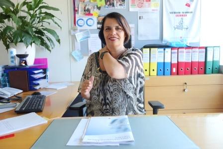 Donna seduta alla scrivania che si massaggia i muscoli del collo con la mano sinistra, tenendo il braccio destro aderente al torace e piegato a 90 gradi, con la mano aperta che punta in avanti